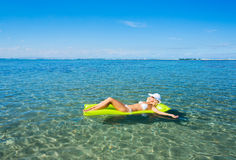 Woman floating on raft in tropical ocean Royalty Free Stock Images