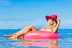 Woman floating on raft in tropical ocean Stock Photography