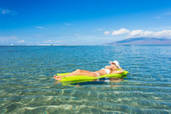 Woman floating on raft in tropical ocean Royalty Free Stock Photos