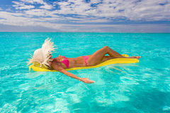 Woman floating on raft in tropical water. Woman relaxing on inflatable raft in turquoise water Royalty Free Stock Images