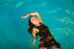 Woman floating relaxing in swimming pool water. Royalty Free Stock Images