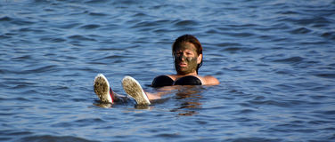 A woman floating in the salty water of the dead sea. DEAD SEA ISRAEL 27 10 16: A woman floating in the salty water of the dead sea. The Dead Sea is 304 m 997 ft Stock Photography