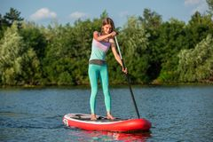 Woman is floating on a SUP board on sunny morning. Stand up paddle boarding - awesome active recreation during vacation. Yoga on sup board with paddle stock photos