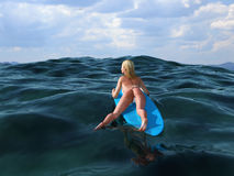 Woman floating on a surfboard Royalty Free Stock Image