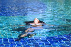 Woman floating in swimming pool royalty free stock photo