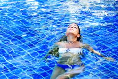 Woman floating in swimming pool royalty free stock images