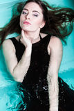 Woman floating on swimming pool in black dress. Stock Photography