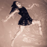 Woman floating on swimming pool in black dress. Stock Photos