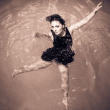 Woman floating on swimming pool in black dress. Stock Photo