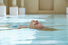 Woman Floating In Swimming Pool royalty free stock photos