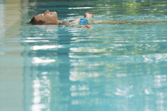 Woman Floating In Swimming Pool stock photo