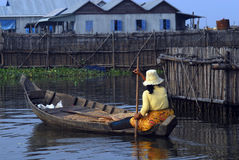 Woman and floating village, Cambodia. A woman paddling a dugout canoe through a floating village on Siem Reap lake in the rainy season Stock Photos
