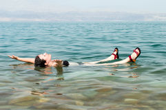 Woman floating in water of dead sea. Woman floating in a glassy water of dead sea with outstretched arms Royalty Free Stock Images