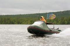Woman floats fishing boat Royalty Free Stock Photo