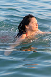 The woman floats in the sea Stock Photos