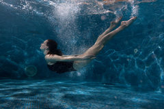 Woman floats under water in the pool. Royalty Free Stock Photography