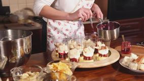 Woman is flooding a fruit dessert by berries liquid marmalades in a kitchen. Confectioner woman is standing on a kitchen and putting layer of jam in desserts stock video footage