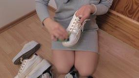 Woman on the floor clean sneakers. In room stock video