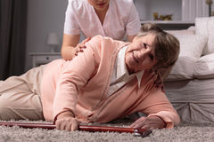 Woman on floor. Disabled older women on floor and caring young assistant royalty free stock images