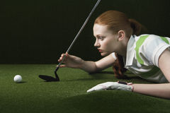 Woman On Floor Holding Golf Club Looking At Golf Ball. Side view of young woman reclining on floor holding golf club looking at golf ball Royalty Free Stock Images