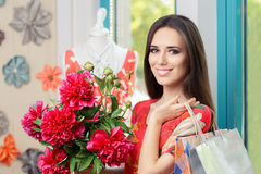 Woman with Floral Bouquet and Shopping Bags Royalty Free Stock Images