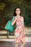 Woman in Floral Dress Holding Stylish Purse Stock Photo