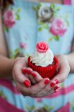 Woman in Floral dress with painted nails holding rose cupcake Stock Photos