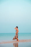 Woman in a floral dress sitting in shallow ocean water. Girl in the sea. Stock Images