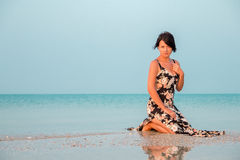 Woman in a floral dress sitting in shallow ocean water. Girl in the sea. Stock Photos
