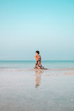 Woman in a floral dress sitting in shallow ocean water. Girl in the sea. Royalty Free Stock Images