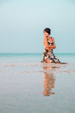 Woman in a floral dress sitting in shallow ocean water. Girl in the sea. looking into the distance. Royalty Free Stock Photography