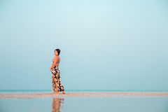Woman in a floral dress sitting in shallow ocean water. Girl in the sea. Royalty Free Stock Photo
