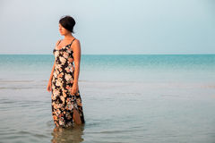 Woman in a floral dress standing in shallow ocean water. Girl in the sea. Royalty Free Stock Photography