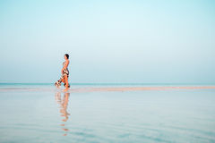 Woman in a floral dress standing in shallow ocean water. Girl in the sea. Royalty Free Stock Photos