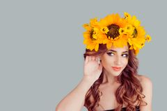 Woman with floral headband with hand to ear listening. Noisy woman with floral headband with hand to ear listening. Fashion girl with crown from sunflowers on royalty free stock photography
