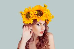 Woman with floral headband hand to ear listening in shock. Closeup portrait of Noisy Caucasian Fashion girl with crown from sunflowers on head hand to ear royalty free stock photography