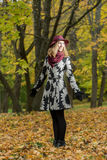 Woman in a floral patterned coat and wine red hat in the park, by the river. Happy girl, colorful autumn forest. Portrait of lady Royalty Free Stock Photography