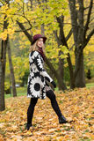 Woman in a floral patterned coat and wine red hat in the park, by the river. Happy girl, colorful autumn forest. Portrait of lady Stock Photo