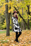 Woman in a floral patterned coat and wine red hat in the park, by the river. Happy girl, colorful autumn forest. Portrait of lady Royalty Free Stock Image