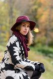 Woman in a floral patterned coat and wine red hat in the park, by the river. Happy girl, colorful autumn forest. Portrait of lady Royalty Free Stock Photos