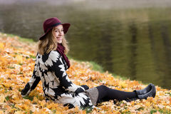 Woman in a floral patterned coat and wine red hat in the park, by the river. Happy girl, colorful autumn forest. Portrait of lady Stock Images