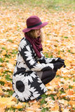 Woman in a floral patterned coat and wine red hat in the park, by the river. Happy girl, colorful autumn forest. Portrait of lady Stock Photos