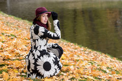 Woman in a floral patterned coat and wine red hat in the park, by the river. Happy girl, colorful autumn forest. Portrait of lady Stock Image