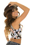Woman in floral shirt cowgirl back hand on hat Royalty Free Stock Photo