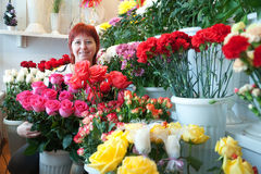 Woman in floral store. Woman in the store surrounded by different flowers Stock Photos