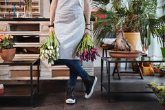 Woman florist in apron and sneakers with two tulips bouquets Stock Photos