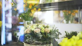 Woman florist arranging flowers in shop window. Close up of a woman florist arranging flowers in vases and baskets in her shop window. Locked down real time stock video