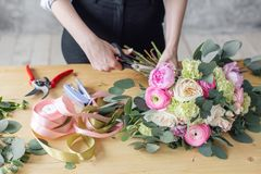 Woman florist creating beautiful bouquet in flower shop. Working in flower shop. Girl assistant or owner in floral. Design studio, making decorations and royalty free stock photo