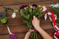 Woman florist creating winter bouquet. Stock Photo