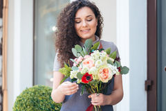 Woman florist with flower bouquet standing in front of shop Stock Images